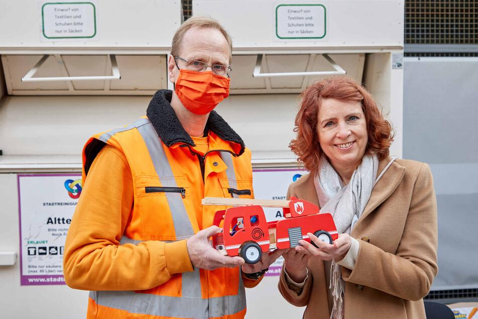 Monica Lierhaus übergibt ein Spielzeug an Jan Henning, Mitarbeiter des Recyclinghofs und Baggerfahrer.