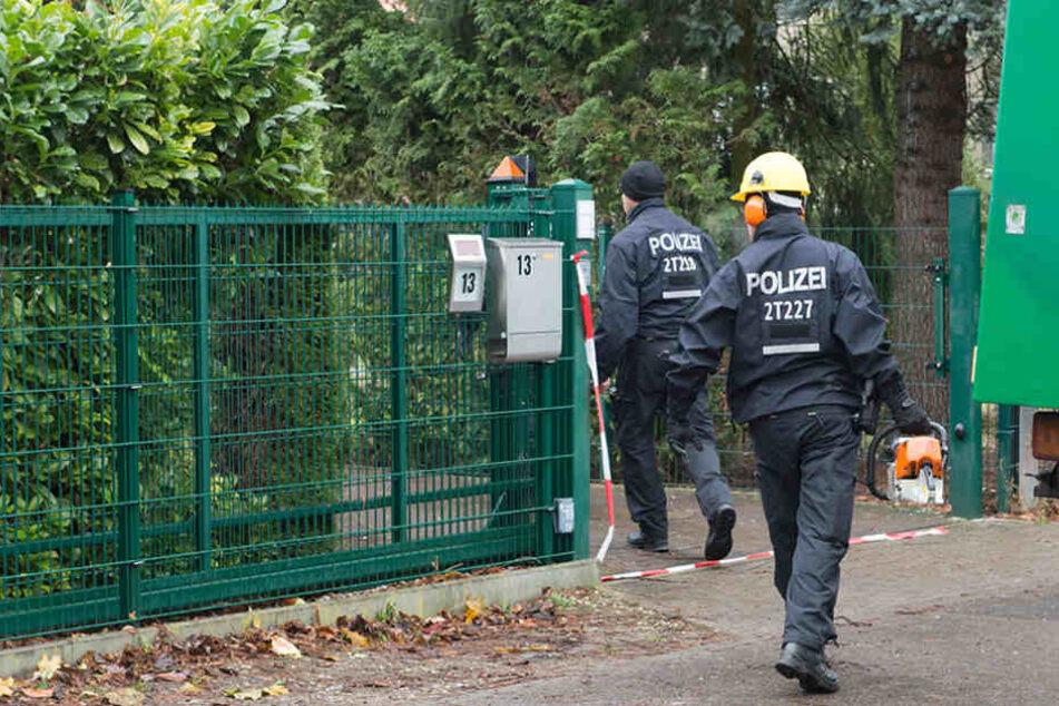 Polizisten betreten mit einer Motorsäge das Grundstück, auf welchem ein Einfamilienhaus eingestürzte.