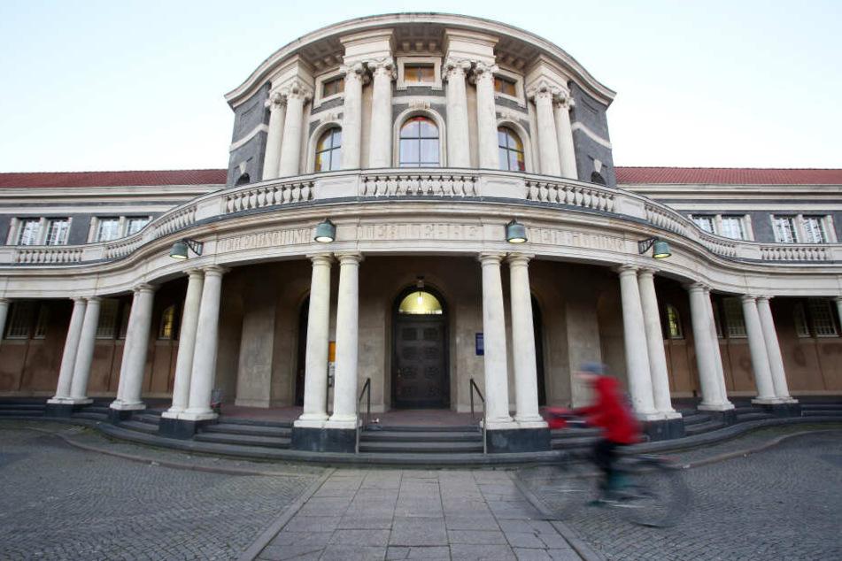 Eine Frau fährt mit einem Fahrrad an dem Hauptgebäude der Universität Hamburg vorbei.