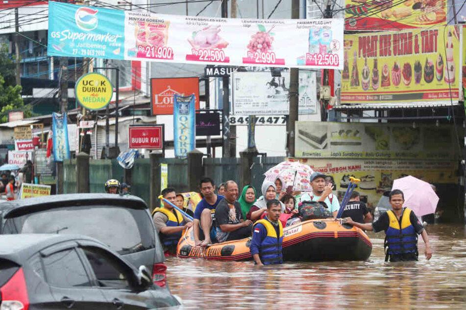 Rettungskräfte evakuieren mit Schlauchbooten Einwohner aus ihren überfluteten Häusern in Jatibening am Stadtrand von Jakarta.