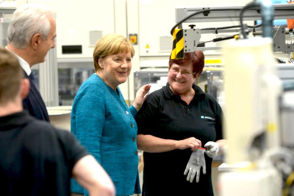Kanzlerin Angela Merkel (62, CDU) spricht beim Rundgang mit Arbeiterin Bettina Wallicke (li.).