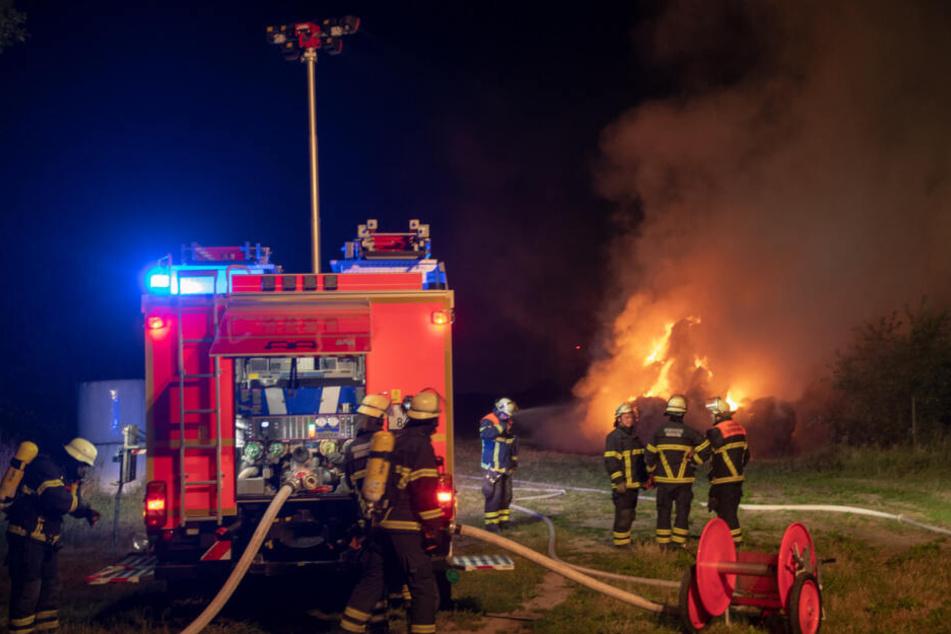 Einsatzkräfte stehen vor den brennenden Heuballen.
