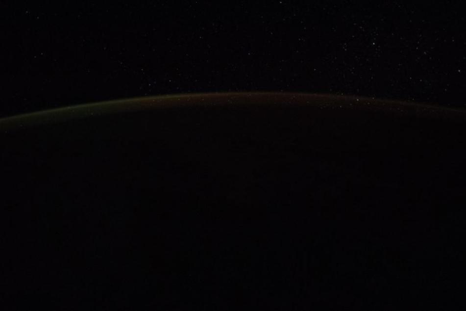 Wer genau hinsieht, sieht einen hellen Streifen am Horizont der Erde.