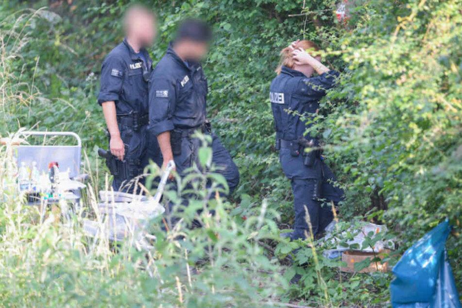 Polizisten suchen den Fundort der Leiche im Gebüsch ab. (Symbolbild)