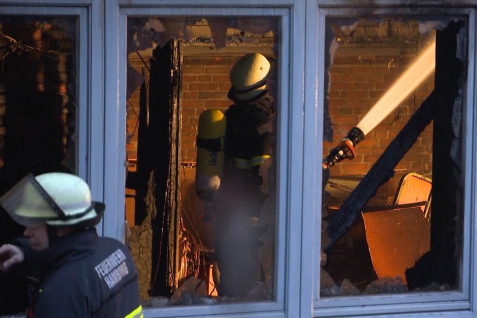 Ein Feuerwehrmann löscht letzte Brandreste in der Hamburger Grundschule.