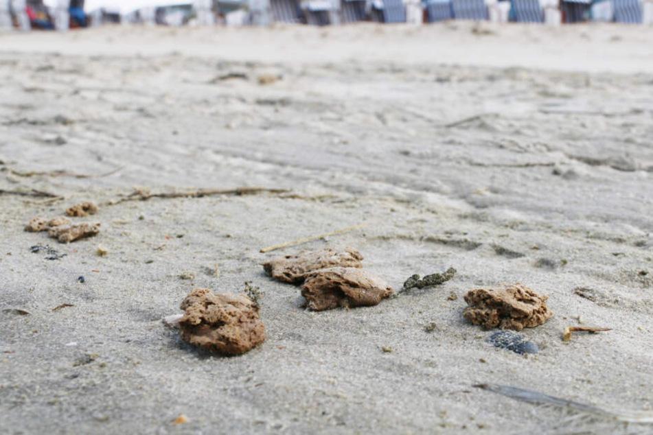 Die Klumpen liegen in nahen Abständen am Strand nahe der Strandkörbe.