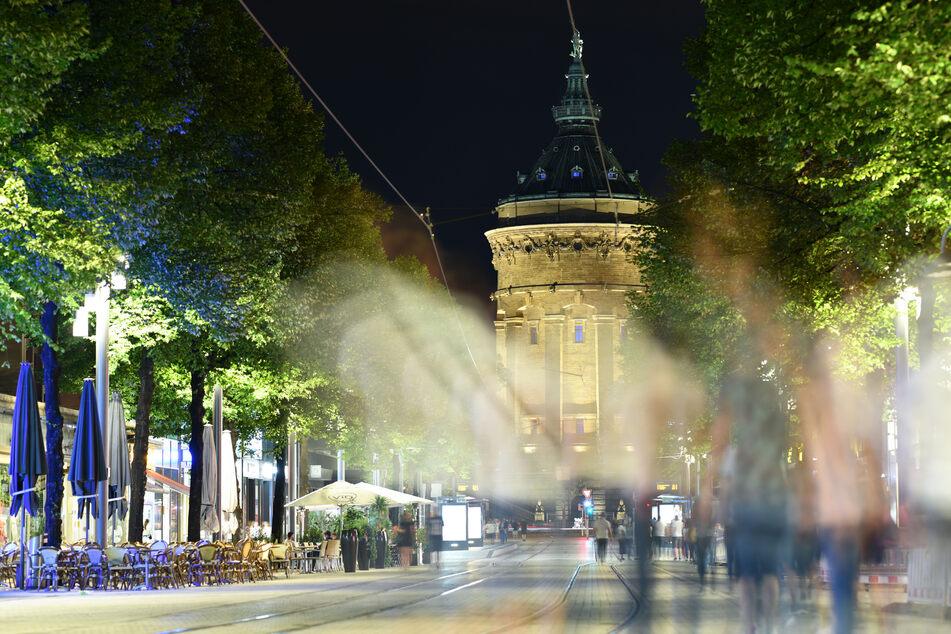 Menschen gehen am späten Abend in der Fußgängerzone Mannheims vor dem Wasserturm.