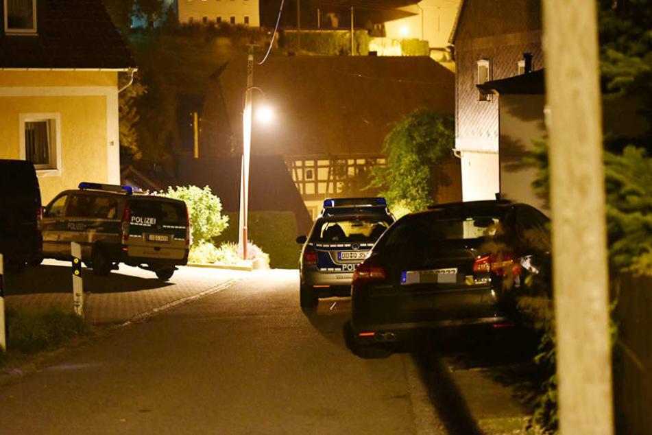 Mehrere Einsatzfahrzeuge der Polizei stehen vor dem Wohnhaus, in dem sich der Täter verschanzte.
