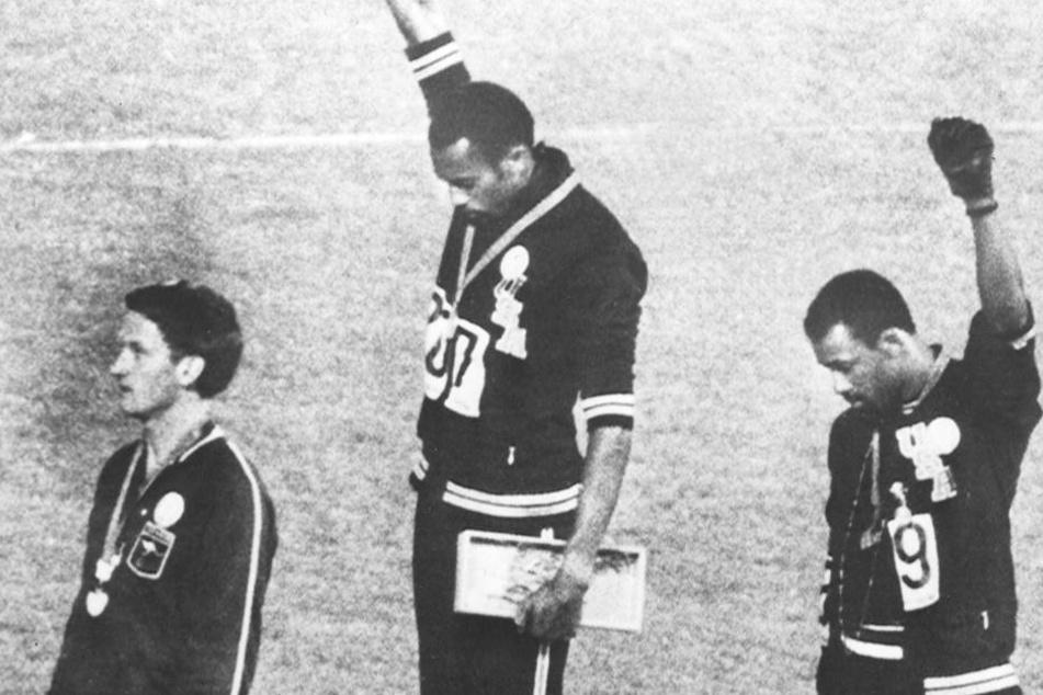 Tommie Smith (M.) und John Carlos heben bei der Siegerehrung der Olympischen Spiele 1968 die Faust als Symbol der Black-Power-Bewegung.