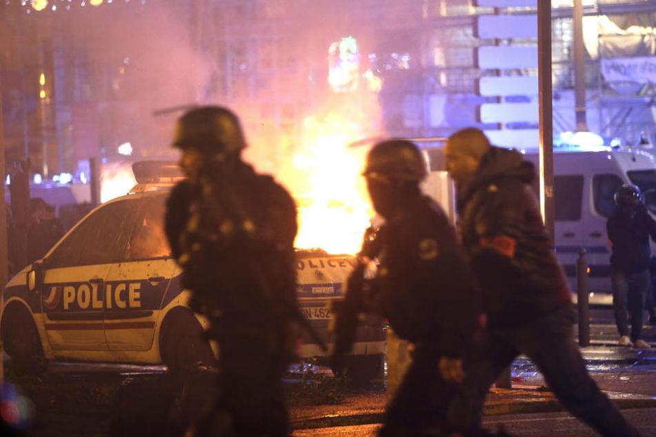 Die Polizei nimmt Position in der Nähe eines brennenden Polizeiwagens ein, bei einem Protest der sich gegen den Sanierungsstau in der Stadt richtet.