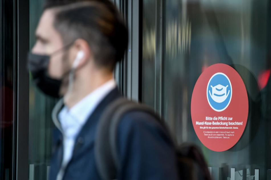 """Am Eingang vom Berliner Hauptbahnhof hängt ein Schild mit der Aufschrift """"Bitte die Pflicht zur Mund-Nase-Bedeckung beachten!""""."""