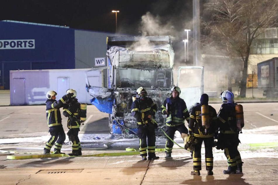 Die Feuerwehrkräfte stehen vor dem ausgebrannten Führerhaus.