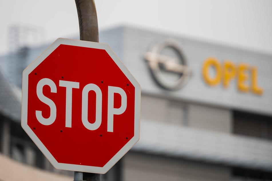 Ein Stop-Schild steht vor dem Opel-Logo. Rund 15.000 Mitarbeiter des Autobauers Opel in Deutschland müssen sich auf Einschnitte bei ihrer betrieblichen Altersvorsorge einstellen.