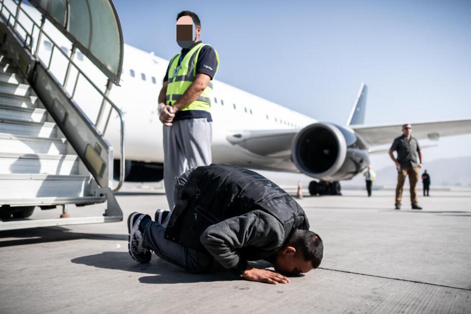 Nach der Landung in Kabul küsst dieser Afghane den Boden seines Heimatlandes.