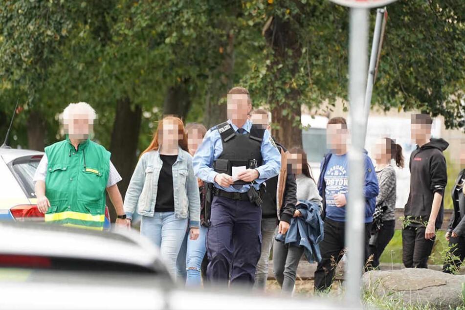 Ein Polizist führt die Schüler zum Sammelplatz.
