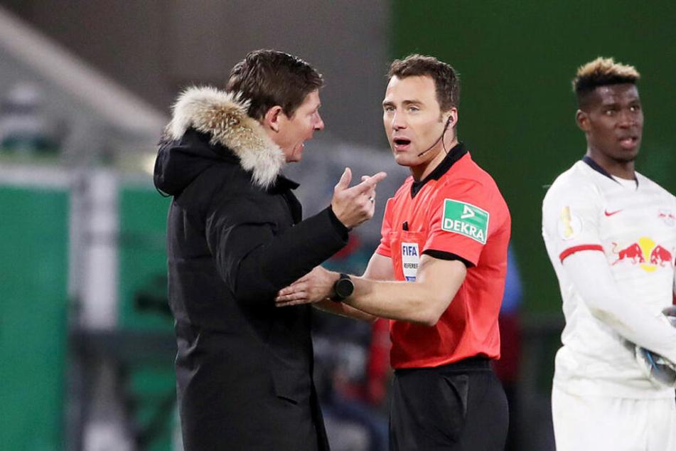 Schiedsrichter Felix Zwayer (r.) musste Wolfsburgs Trainer Oliver Glasner erklären, weshalb er das Handspiel von Yussuf Poulsen nicht abgepfiffen hat.