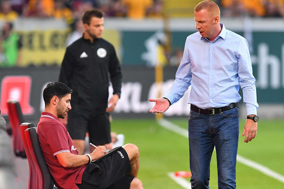 Dynamo-Coach Maik Walpurgis (r.) nimmt während eines Spiels kurz Rücksprache mit seinem am Tablet arbeitenden Co-Trainer Ovid Hajou und holt sich dabei wichtige, möglicherweise sogar spielentscheidende Informationen.