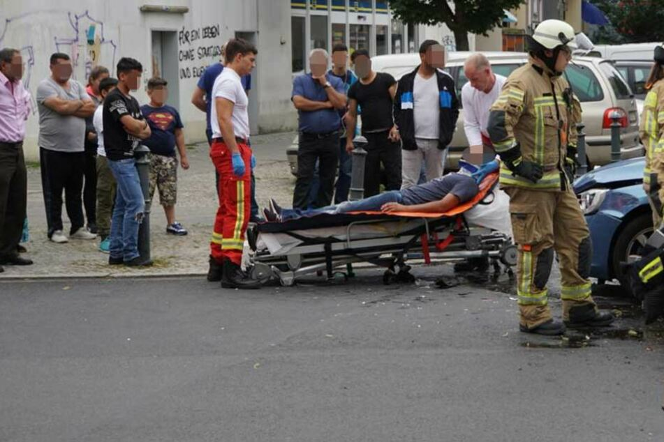 Der Mann liegt mit einer Halskrause auf der Trage und die Schaulistigen starren ihn unvermittelt an.