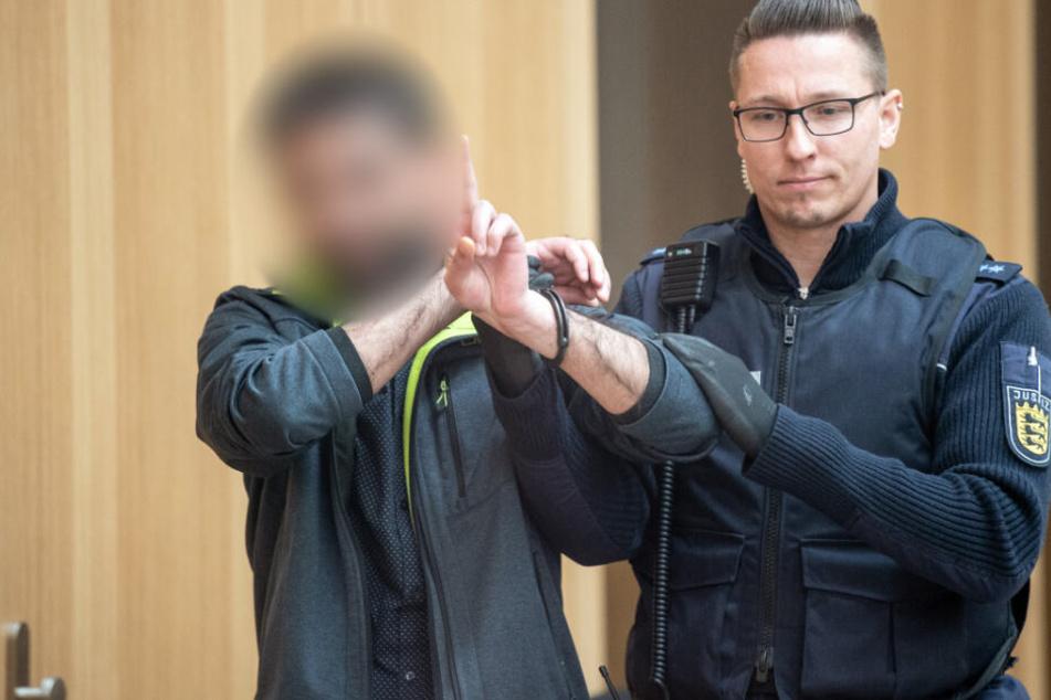 Dieser Angeklagte gestikuliert mit den Händen, während er in den Gerichtssaal gebracht wird.