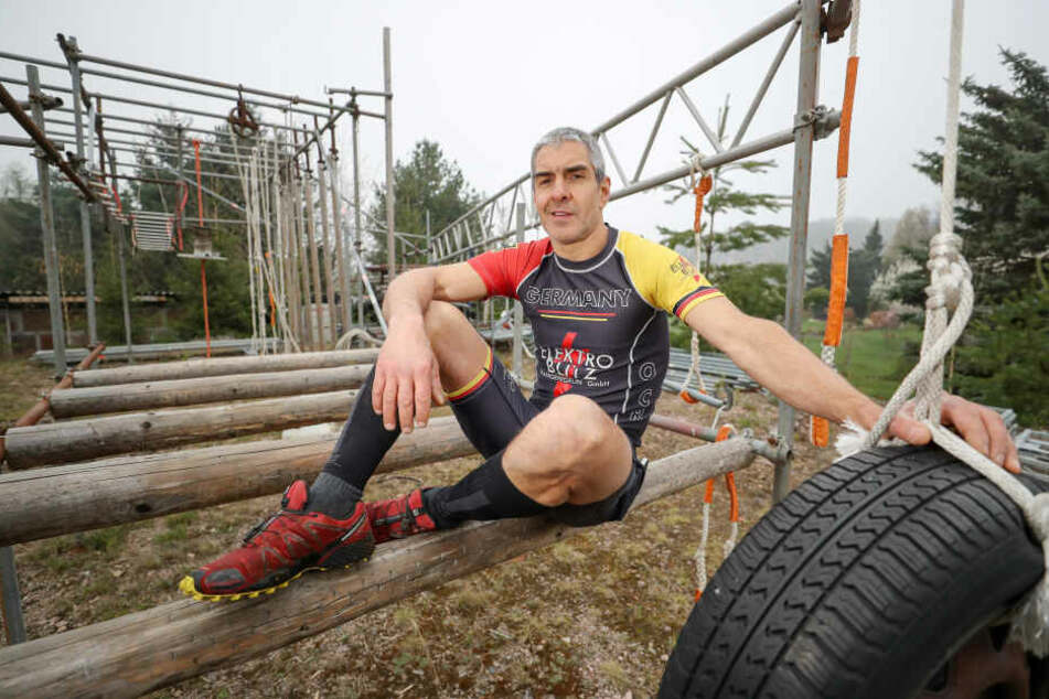 Jörg Eißmann sitzt auf seinem selbstgebauten Parcours für das Training im Extremhindernislauf.