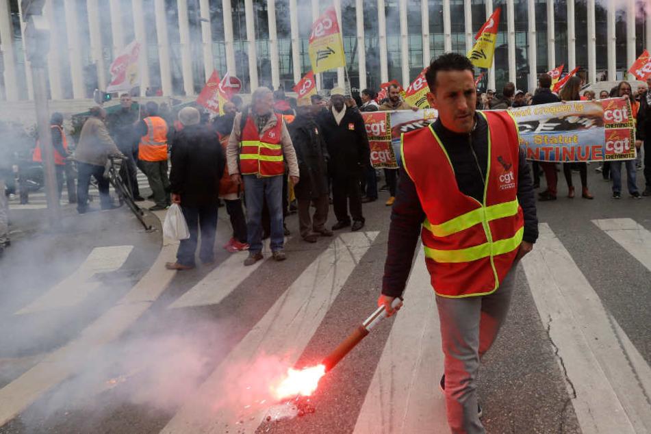 Ein Demonstrant hält bei einem Protest vor dem Bahnhof Saint Charles in Südfrankreich eine Fackel in der Hand. (Archivbild)