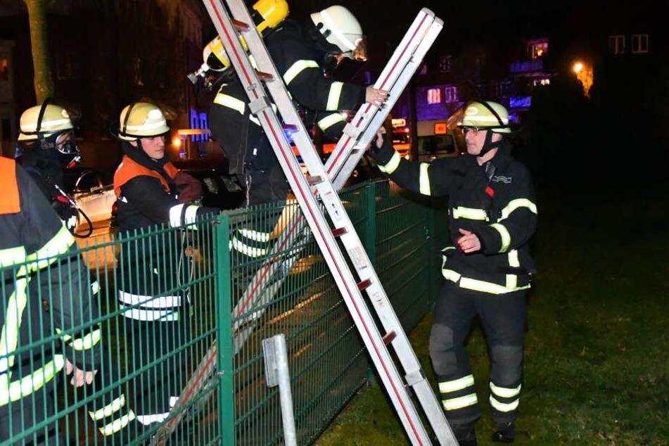Die Feuerwehrleute mussten über einen Zaun klettern, um das Feuer zu erreichen.