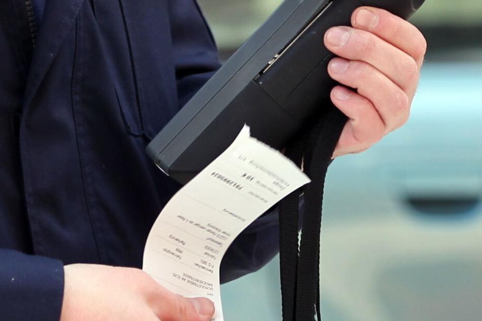 Ein Verkehrspolizist druckt einen Strafzettel aus. (Symbolbild)