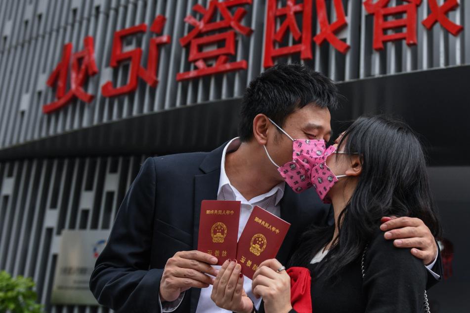 Ein Paar mit Mundschutz küsst sich, während sie ihre Heiratsurkunden stolz halten.