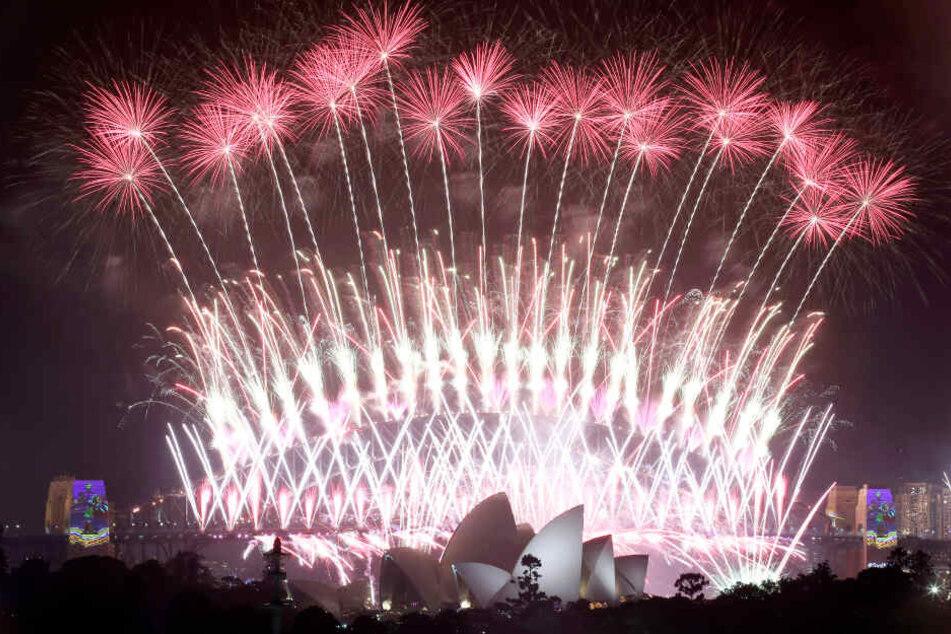 Ein Feuerwerk explodiert am Himmel über Oper und der Harbour Bridge, während der Neujahrsfeierlichkeiten
