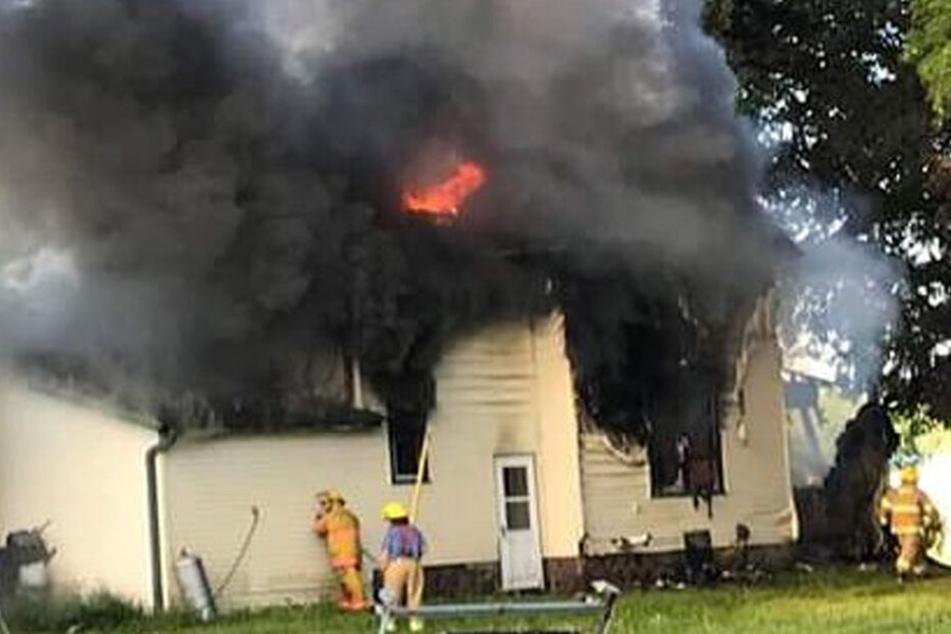 Feuerwehrleute versuchen das Feuer in einem Haus zu löschen.