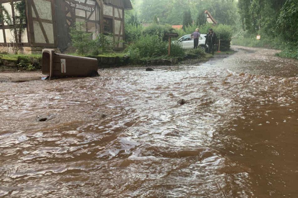 Eine Straße in Gieselwerder ist von Schlammwasser überspült.