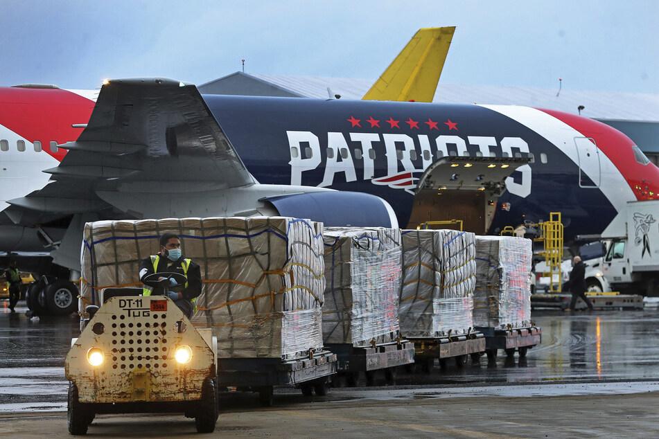 Paletten mit Atemschutzmasken werden aus einem Flugzeug der New England Patriots auf dem Logan Airport in Boston entladen. Das Flugzeug der New England Patriots hat angesichts der Coronavirus-Krise mehr als eine Million Atemschutzmasken aus China Anfang April in die USA geflogen.