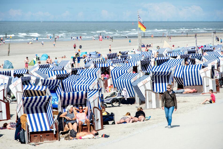 Urlaubsgäste sitzen bei sonnigem Wetter in ihren Strandkörben.
