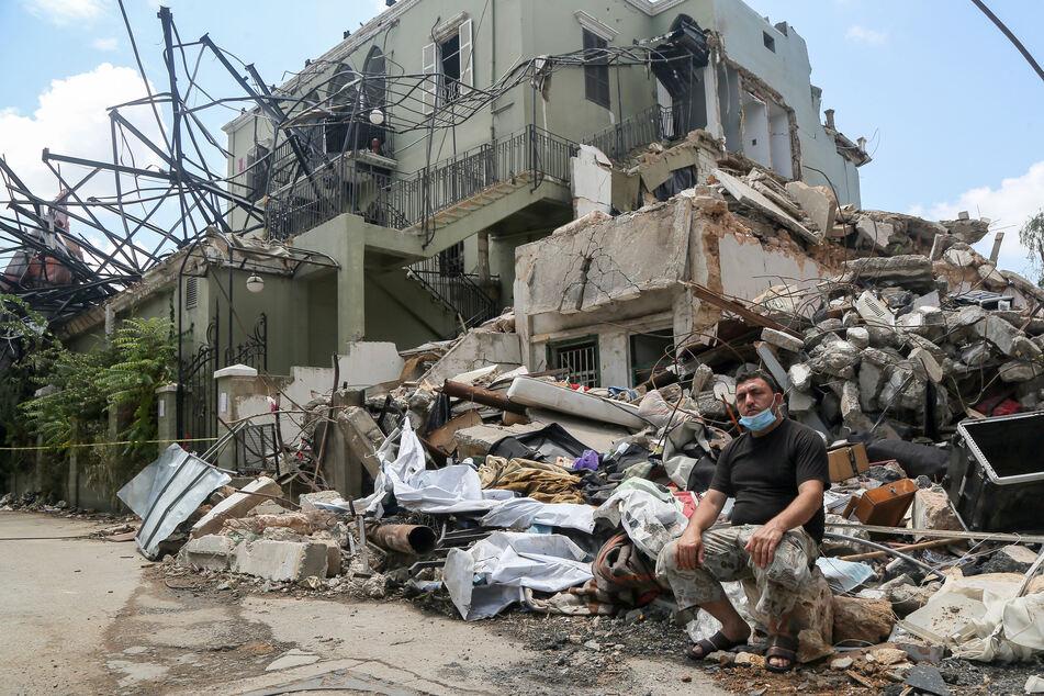 Libanon, Beirut: Der 47-jährige aus Idlib stammende Syrer Ahmad Haj Mustapha sitzt vor den Trümmern seines Hauses, Tage nach der schweren Explosion im Hafen Beiruts.
