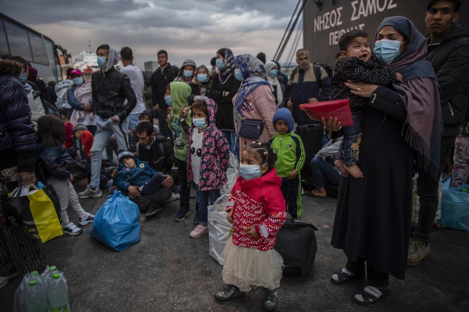 Migranten aus dem Lager Moria, die mit einem Schiff von der Insel Lesbos gekommen sind, gehen im Hafen von Piräus bei Athen an Land.