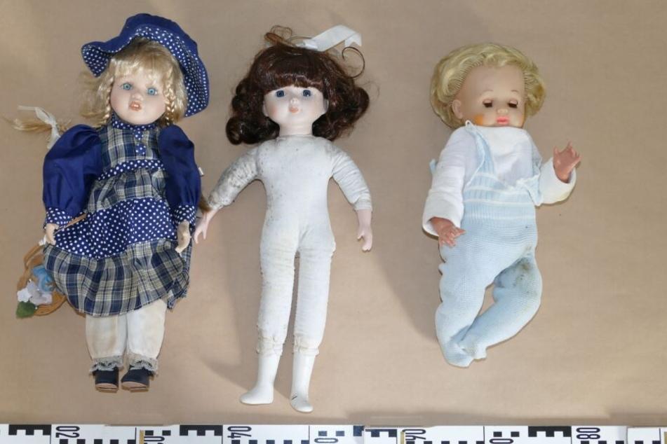 Drei der Grusel-Puppen aus dem Wald liegen auf einem Tisch der Polizei.