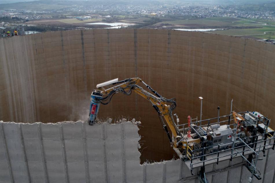Ein ferngesteuerter Bagger knabbert an der Betonkonstruktion.
