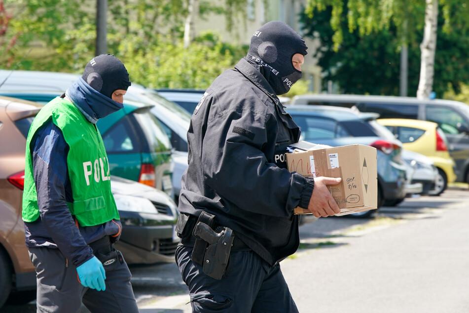 Bundespolizisten tragen in einer Kiste gesicherte Unterlagen aus einem Haus.