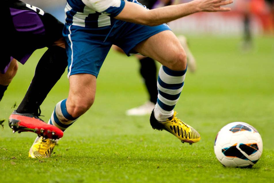 Zwei Fußballspieler kämpfen um den Ball. (Symbolbild)