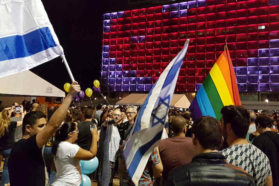 Mit israelischen Flaggen und der Regenbogenfahne feiern Fans der Sängerin Netta Barzilai, die Israel beim Eurovision Song Contest 2018 vertreten hat, den Sieg.