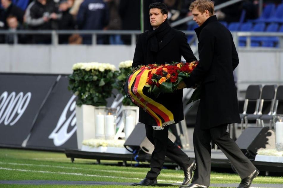 Per Mertesacker (re.) und der ehemalige Nationalmannschaftskapitän Michael Ballack (li.) tragen bei der Trauerfeier im Stadion einen Kranz zum Mittelkreis.