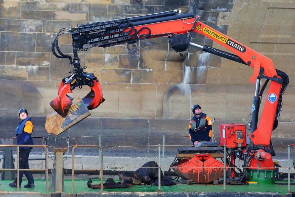 Mit dem Greifer zogen Mitarbeiter des Wasserstraßen- und Schifffahrtsamts gestern einen Sandsteinbrocken aus der Elbe.