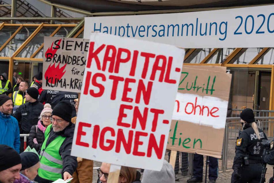 Klimaaktivisten demonstrieren mit Plakaten am Haupteingang zu Beginn der Siemens-Hauptversammlung 2020 vor der Olympiahalle.