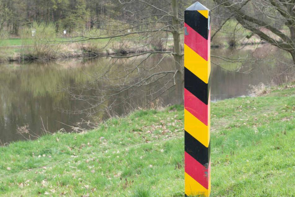 Ein Grenzpfahl markiert am Ufer der Neiße in Görlitz die deutsch-polnische Grenze.