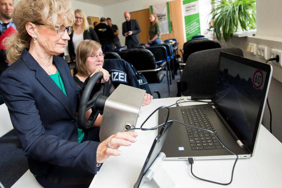 Birgit Keller, Thüringer Ministerin für Infrastruktur und Landwirtschaft versucht sich an einem Fahrsimulator, welcher die verschiedenen Ablenkungen beim Autofahren darstellt. Mandy Passit von der Landesverkehrswacht erklärt ihr das Gerät.