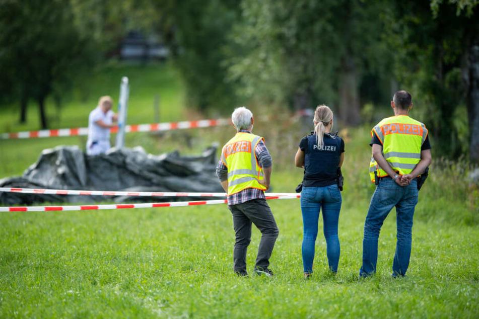 Polizisten stehen an einem abgesperrten Bereich an einem Bachlauf im Ortsteil Scharling. Die vermisste 17-Jährige wurde tot in einem Bachlauf gefunden.