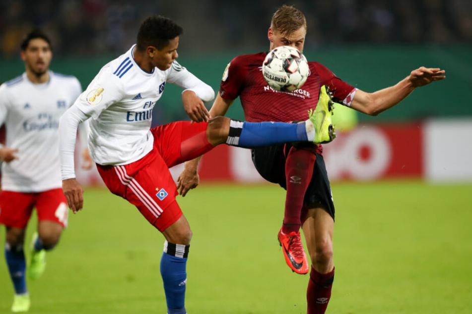 Douglas Santos (links) und Nürnberg-Kapitän Hanno Behrens kämpfen um den Ball.