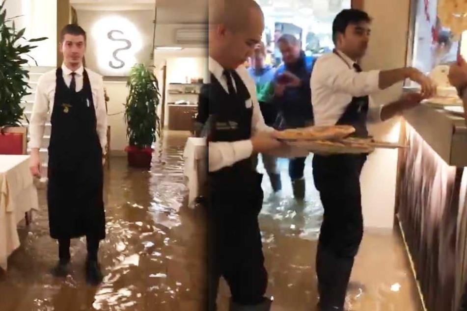 Heftiges Hochwasser, doch diese Pizzeria-Mitarbeiter stört es nicht