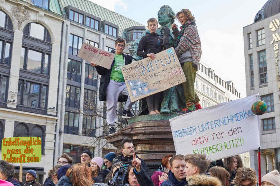 """Klimaaktivisten halten auf dem Lessing-Denkmal am Gänsemarkt Transparente unter anderem mit der Aufschrift: """"Grüne Wende sonst Ende"""" und """"Enkeltauglich muss die Zukunft sein"""" hoch."""