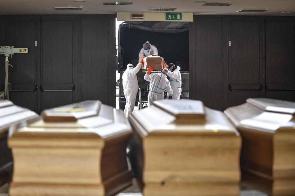 Särge, die aus der Gegend von Bergamo eintreffen, werden von Arbeitern in Schutzanzügen aus einem Militärfahrzeug in ein Gebäude des Friedhofs von Cinisello Balsamo getragen.